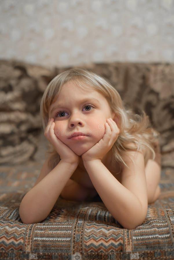 Pojken 4 gamla år hemma ligger på soffan och den hållande ögonen på TV:N blond pojkestående arkivbilder