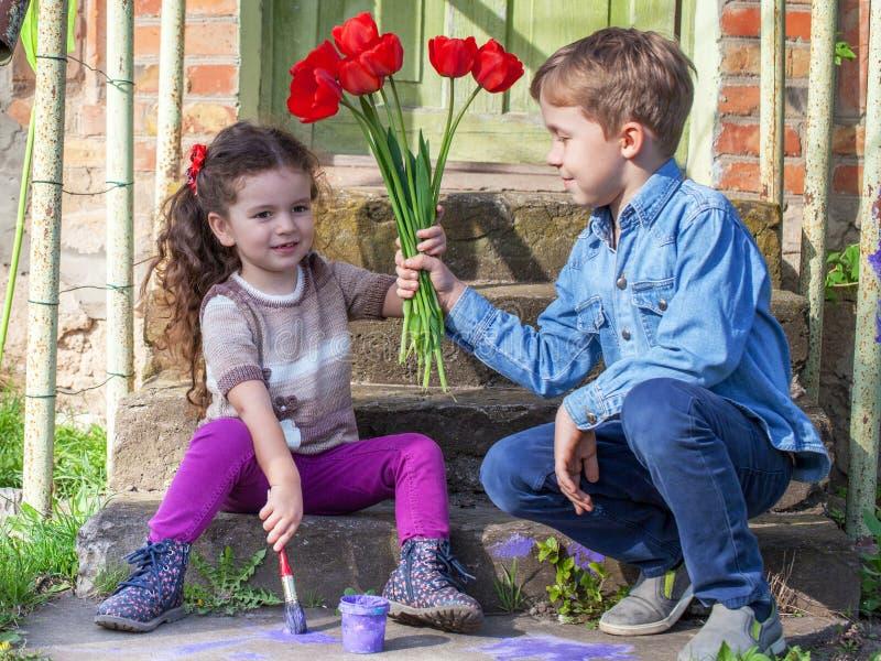 Pojken ger blommor till behandla som ett barn flickan arkivfoto