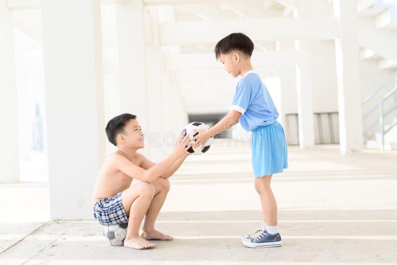 Pojken ger fotboll royaltyfria bilder