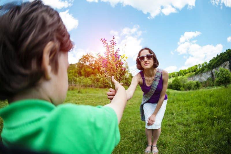 Pojken ger hans moder en bukett av blommor royaltyfri fotografi