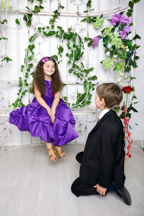 Pojken ger till flickan en rosblomma Lite förälskat royaltyfria bilder