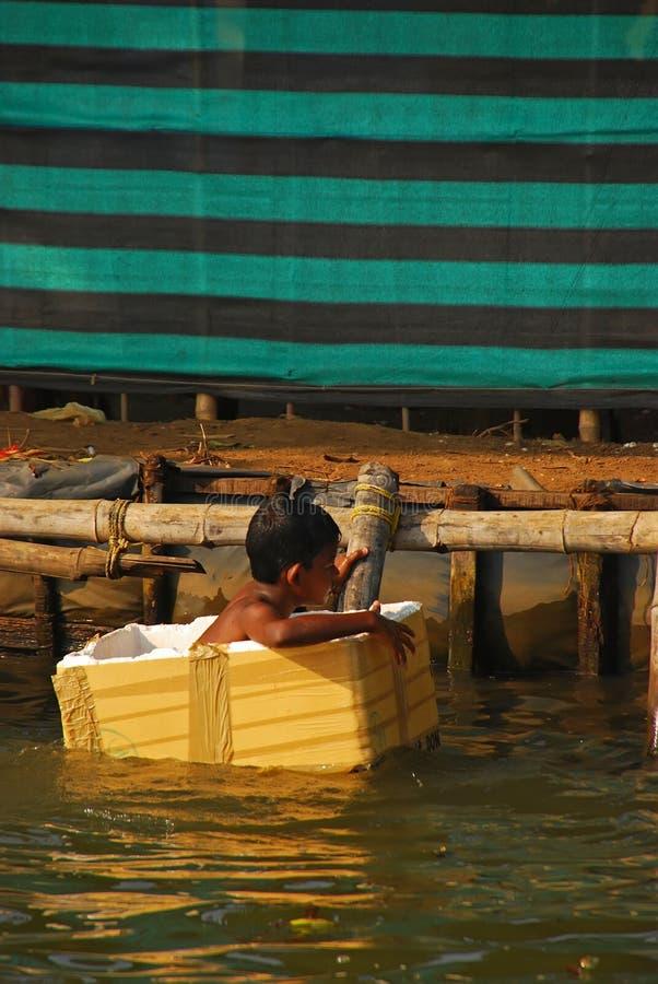 Pojken grundar att sväva inom den vita polystyrenasken på en flodbank på Kerala, Indien royaltyfria foton