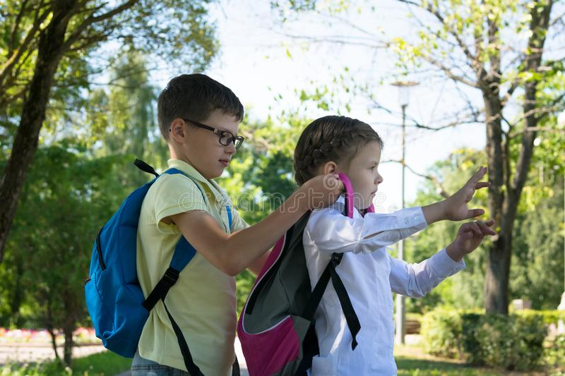 Pojken hjälper flickan att sätta en ryggsäck på hans skuldror, innan han går att skola, skolbarn på gatan royaltyfri bild