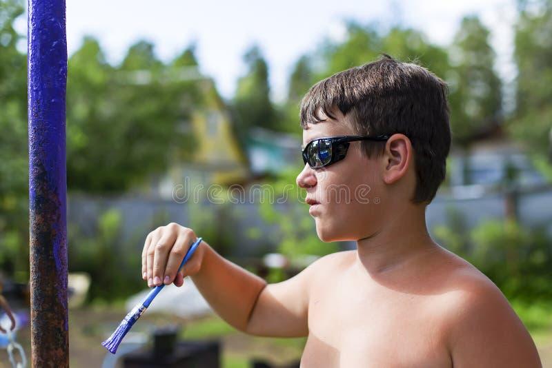 Pojken hjälper i landet, målar ett rör royaltyfria bilder