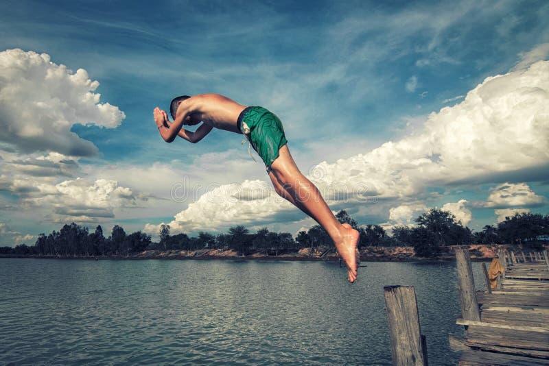 Pojken hoppar in i vattnet arkivbild