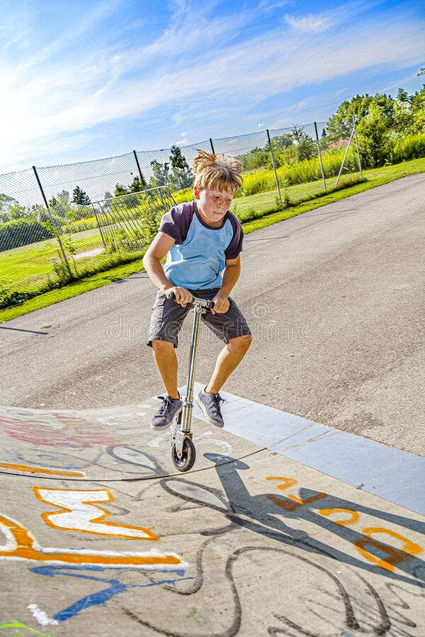 Pojken hoppar med skjutskotrar i skateparken arkivbild