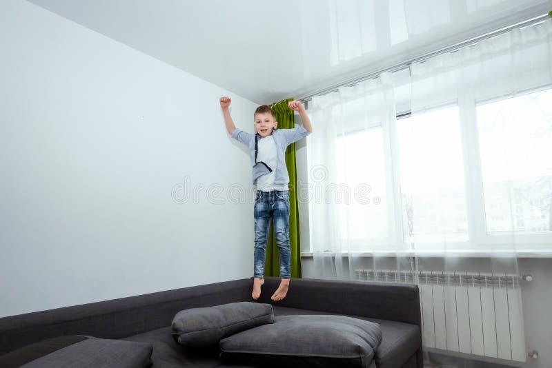 Pojken hoppar på soffan i vardagsrummet och att ha gyckel som omkring bedrar, medan hans föräldrar inte är hemmastadda Behandla s arkivfoto