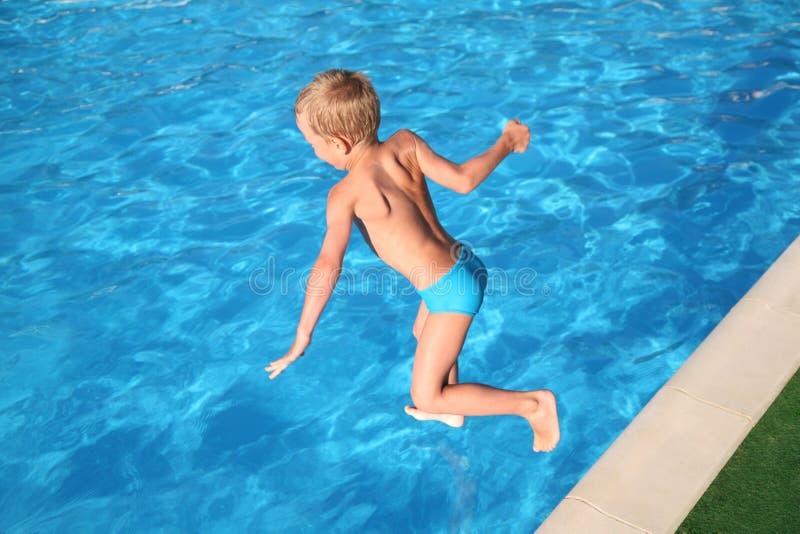 pojken hoppar pölen royaltyfri bild