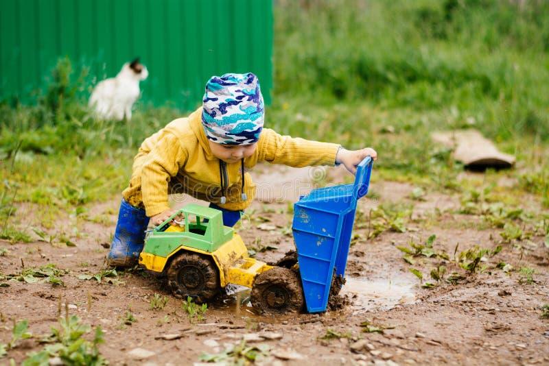 Pojken i den gula dräkten som spelar med en leksakbil i smutsen arkivfoto