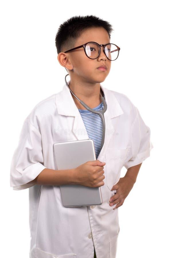 Pojken i den medicinska enhetliga hållande minnestavlan arkivfoto