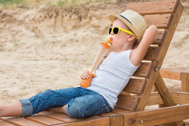 Pojken i den sugrörhatten och solglasögon som ligger på träsoldagdrivaren på stranden och att dricka ny fruktsaft för sommarterri arkivbilder