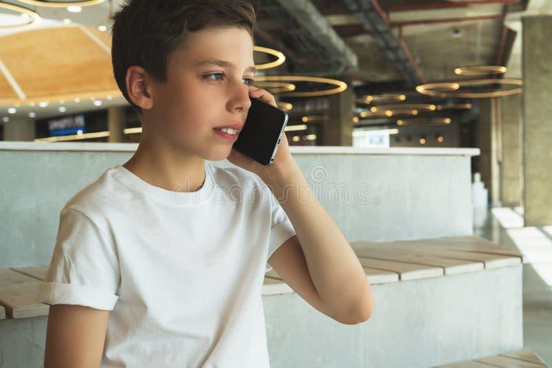 Pojken i den vita t-skjortan sitter inomhus och talar på hans mobiltelefon En tonåring använder en mobiltelefon och att kalla som arkivfoton