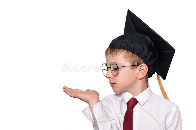 Pojken i en fyrkantig akademisk hatt och exponeringsglas rymmer hans gömma i handflatan upp skola f?r copyspace f?r begrepp f?r s arkivfoto