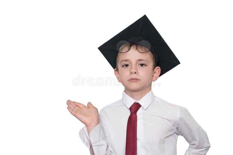 Pojken i en fyrkantig akademisk hatt och exponeringsglas rymmer hans gömma i handflatan upp skola f?r copyspace f?r begrepp f?r s royaltyfria bilder