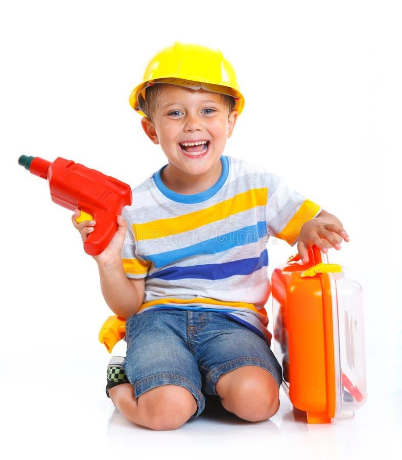 Pojken i en hjälm spelar i byggmästaren arkivfoto