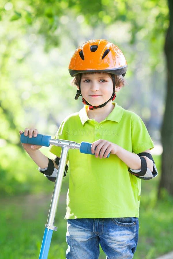 Pojken i en röd säkerhetshjälm står med sparksparkcykeln royaltyfria bilder