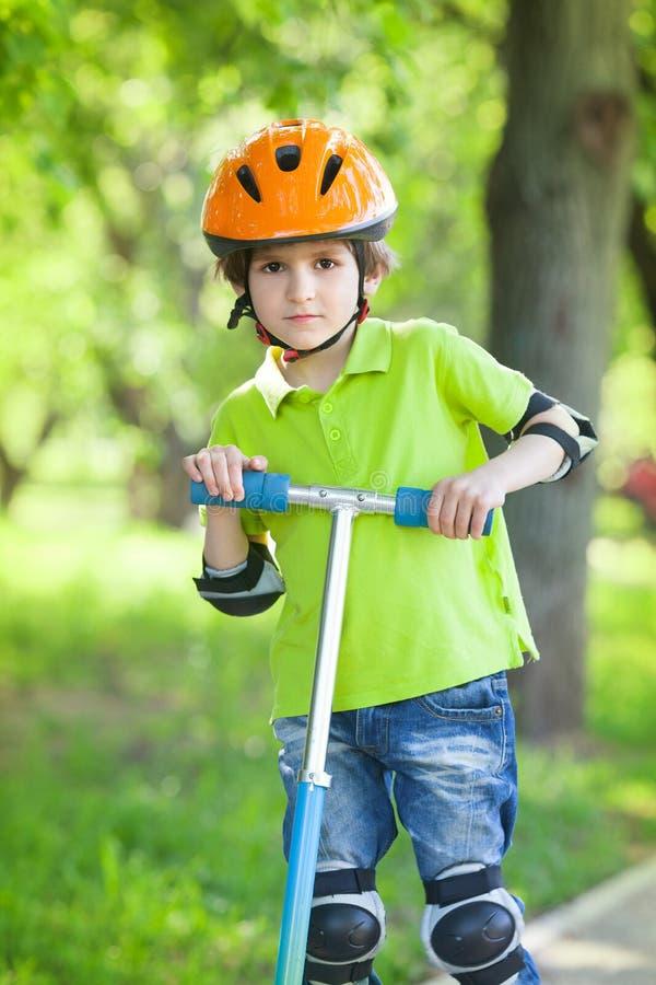 Pojken i en säkerhetshjälm står med sparksparkcykeln arkivbild