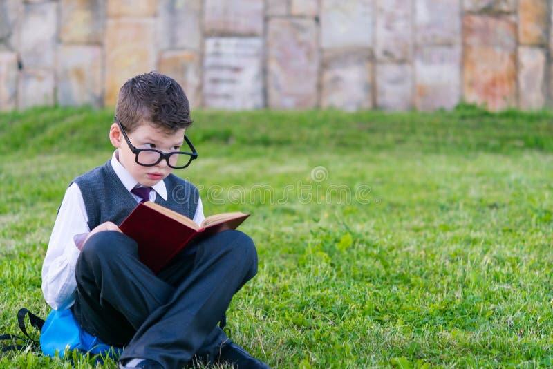 Pojken i exponeringsglas, skolpojkesammanträdegräsmatta som läser en bok, i, parkerar utomhus royaltyfria bilder