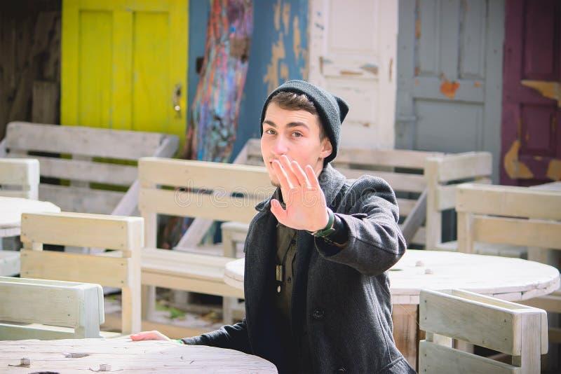 Pojken i gatan som vinkar försiktigt hans hand arkivfoto