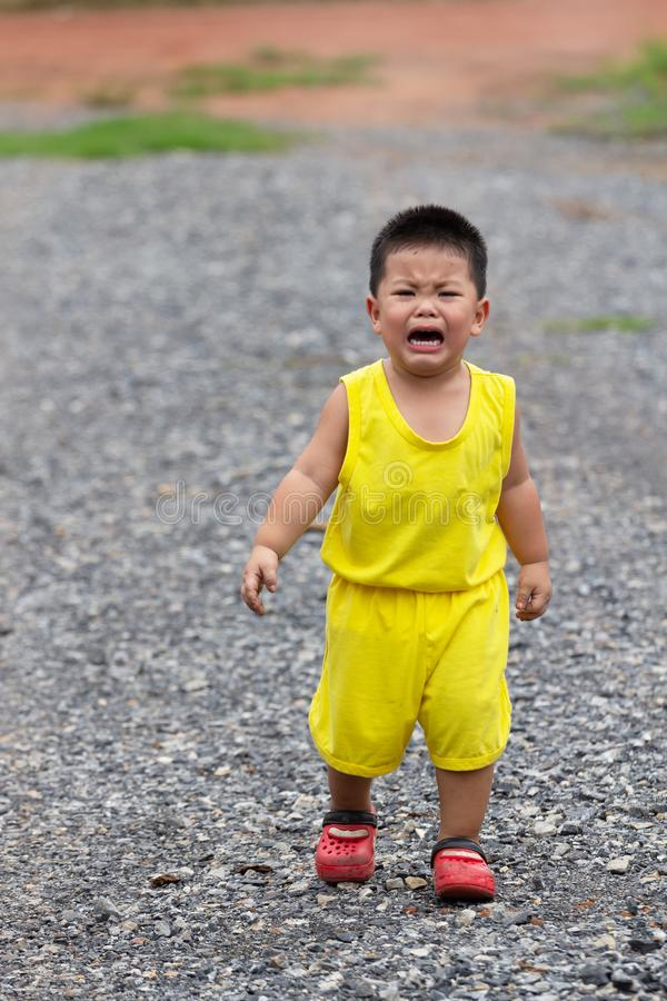 Pojken i gul klänning gråter royaltyfri bild