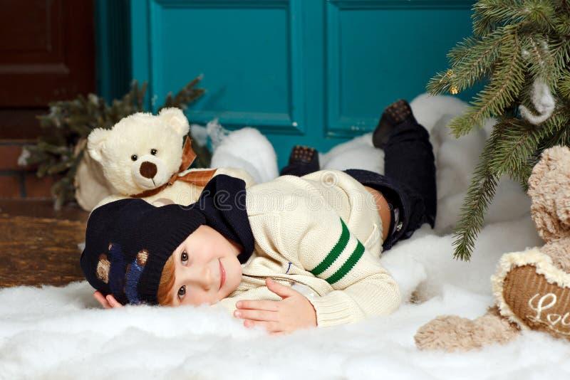 Pojken i hatt ler och ligger på den insnöade julen för en studio royaltyfria foton