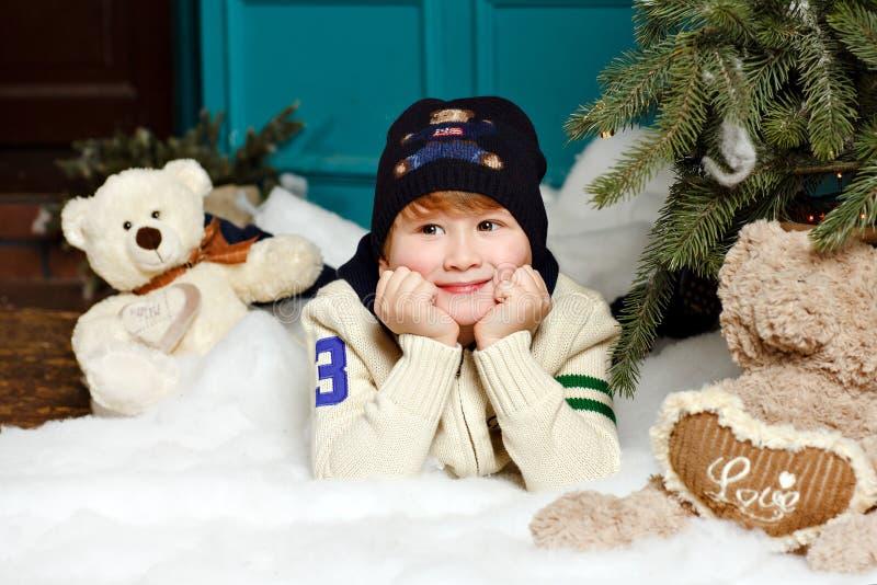 Pojken i hatt ler och ligger på den insnöade julen för en studio royaltyfria bilder