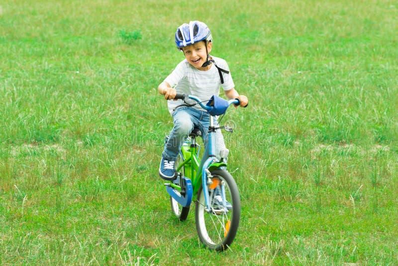 Pojken i jeans och en röd T-tröja som rider en cykel royaltyfri fotografi