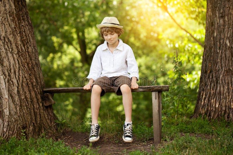 Pojken i kortslutningar sitter på en bänk royaltyfri foto
