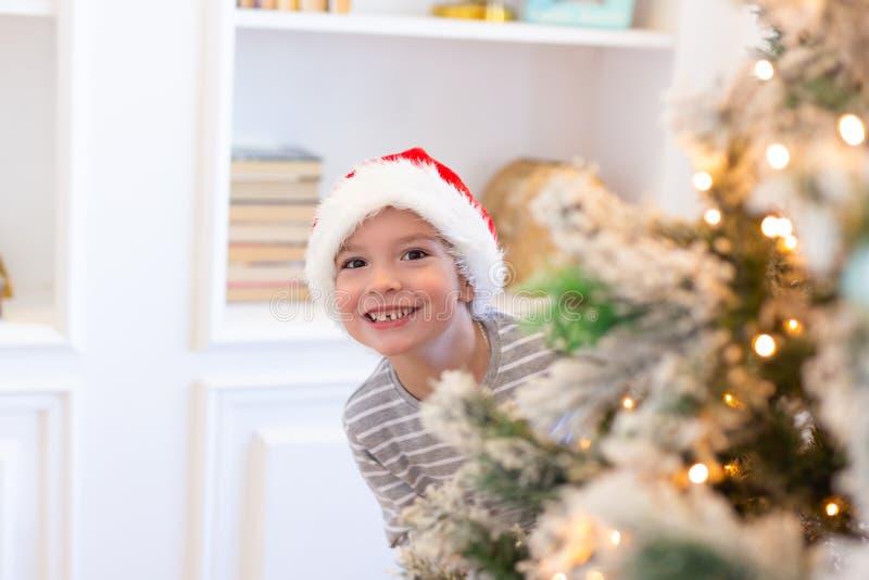 Pojken i santa ser ut från julträd julen dekorerar nya home idéer för garnering till isolerat nytt vitt år för jul begrepp magisk arkivbilder