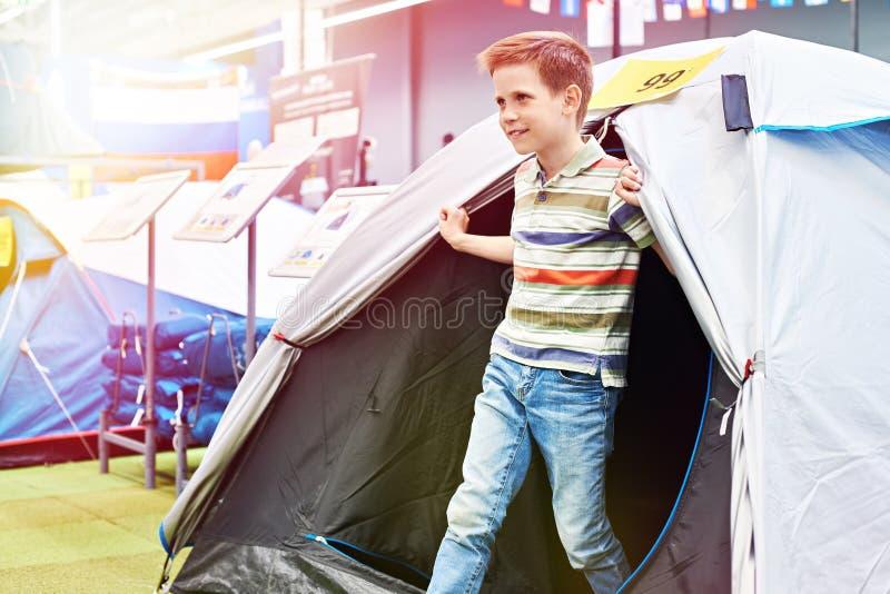 Pojken i turist- tält på sporten shoppar royaltyfria foton