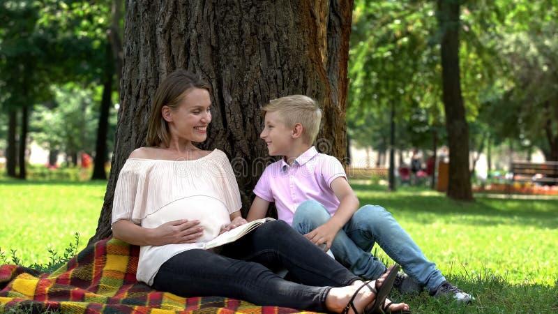 Pojken kör till gravid sund som och lycklig havandeskap in för modern läseboken parkerar, arkivfoton