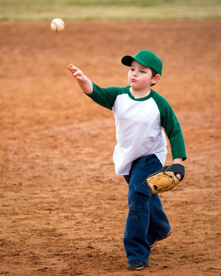 Pojken kastar baseball arkivbilder