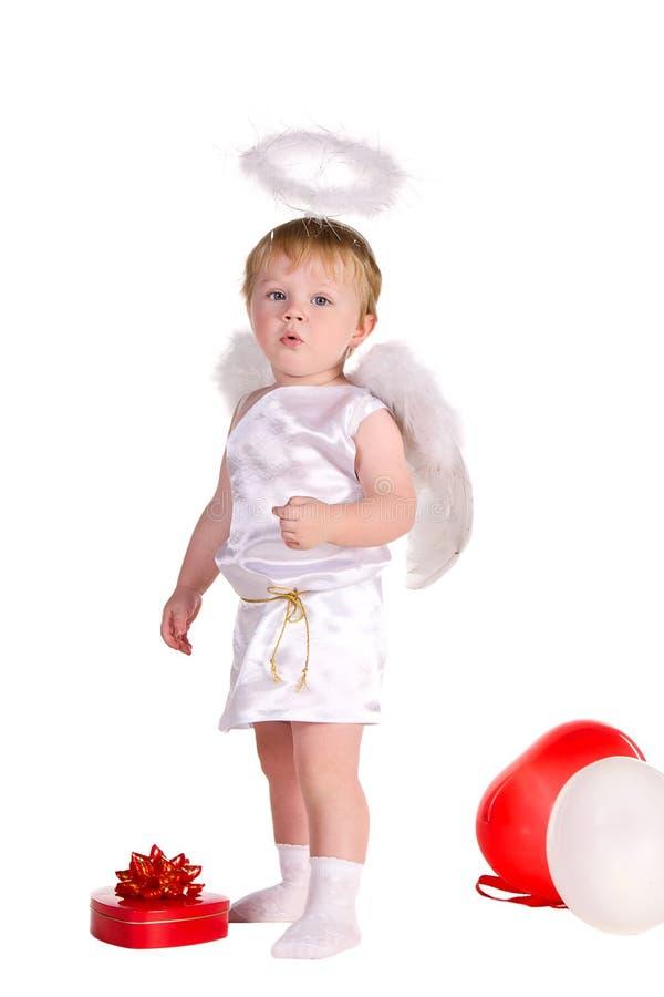 Pojken klädde som ängel med vit och röda ballonger arkivbilder