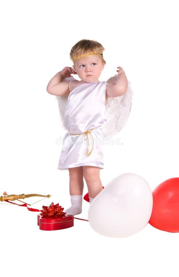 Pojken klädde som ängel med vit och röda ballonger arkivfoto