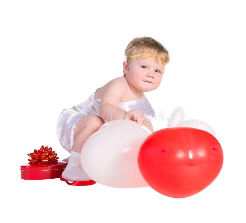 Pojken klädde som ängel med vit och röda ballonger royaltyfria bilder