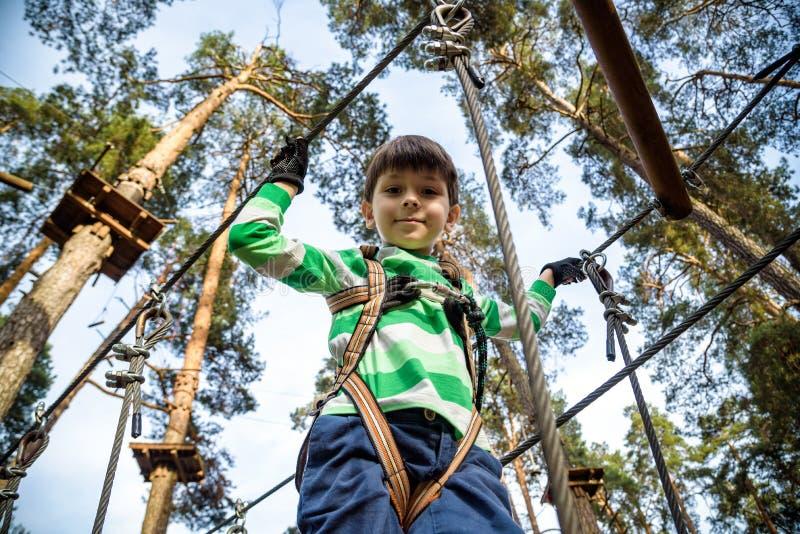 Pojken klättrar i en hög tråd parkerar ovanför jordningen ziplining pojke på vinandelinjen ungen passerar rephinderkursen royaltyfri fotografi
