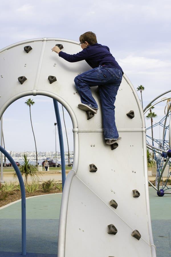 Pojken klättrar lekplatsutrustning royaltyfri fotografi