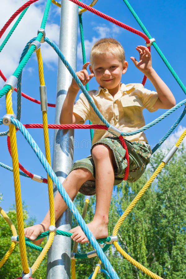 Pojken klättrar repen royaltyfria bilder