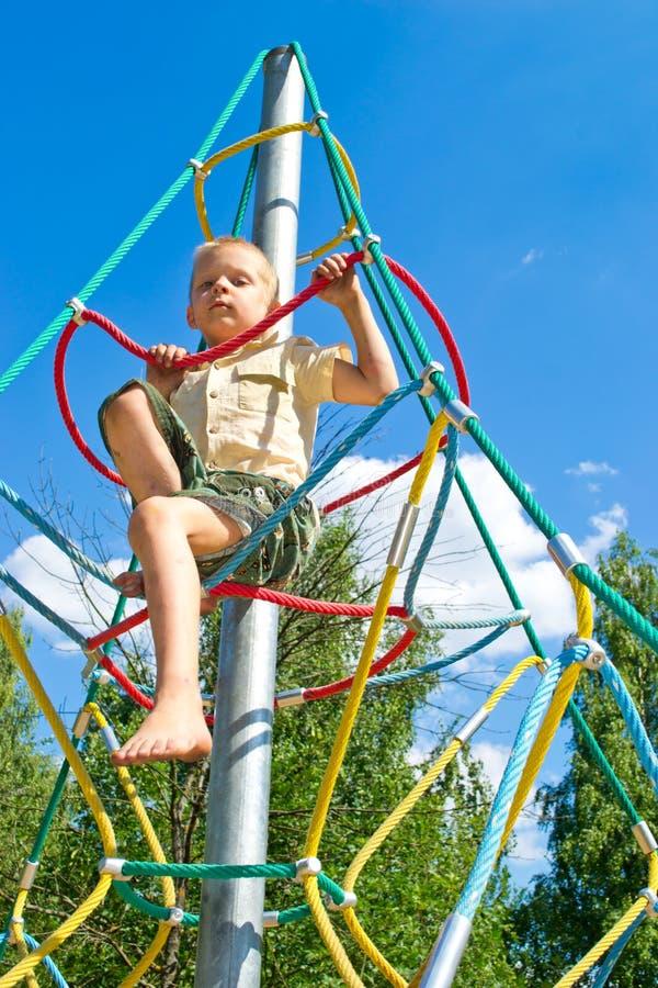 Pojken klättrar repen arkivbild