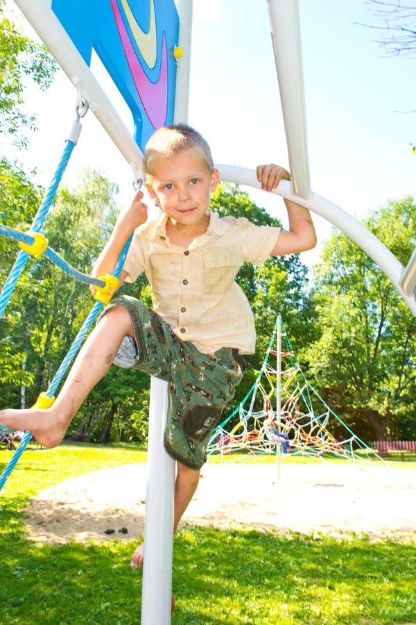 Pojken klättrar repen arkivfoto