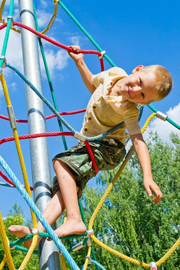 Pojken klättrar repen fotografering för bildbyråer