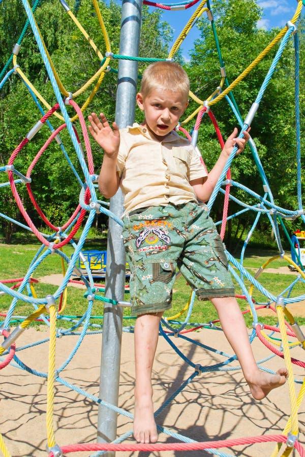 Pojken klättrar repen royaltyfri foto