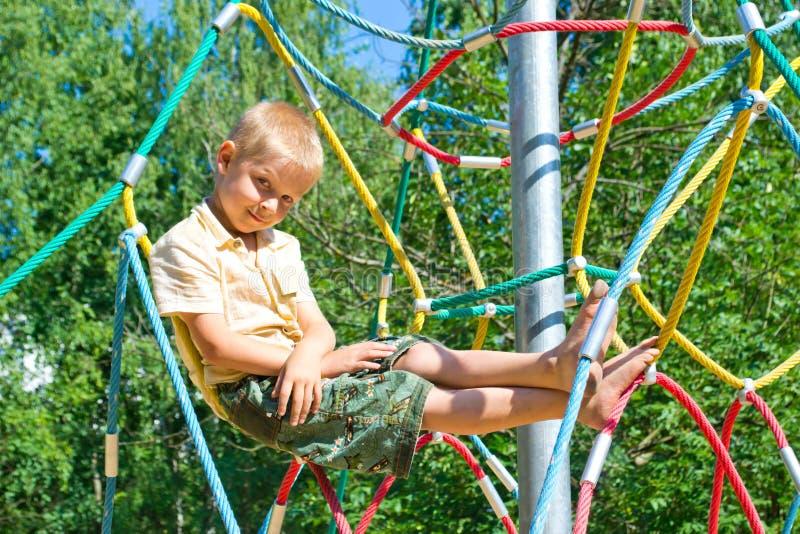 Pojken klättrar repen royaltyfria foton