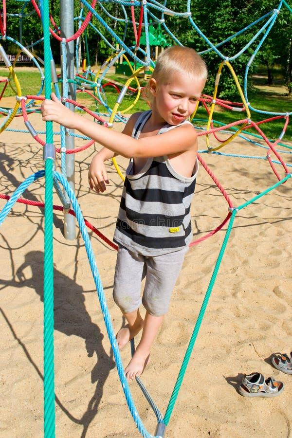 Pojken klättrar repen arkivbilder