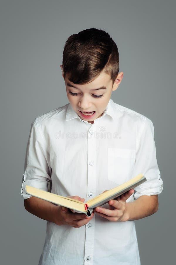 Pojken läser en bok arkivfoto