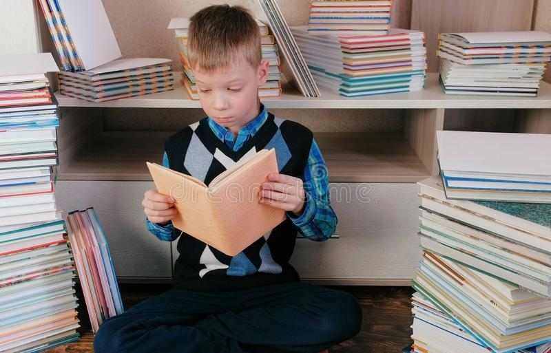 Pojken läser ett boksammanträde på golvet bland böckerna arkivfoto