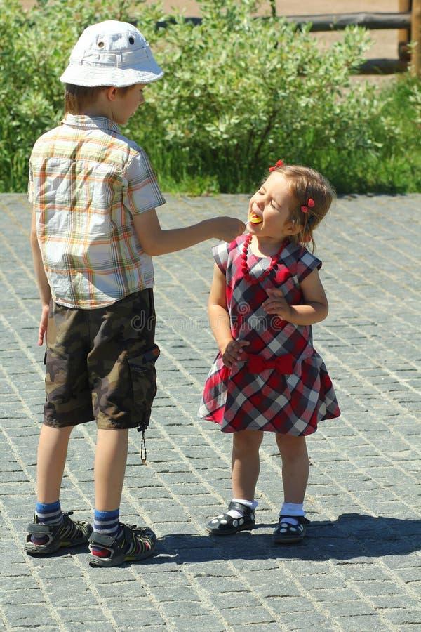Pojken låter hans lilla syster smaka klubbagodisen arkivfoto