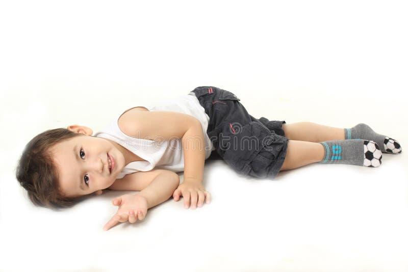 Pojken ligger ner på golvet royaltyfria foton