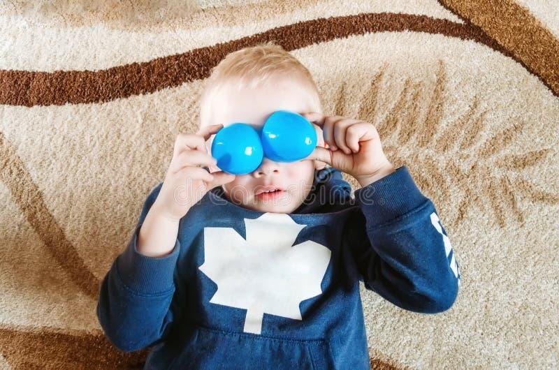Pojken ligger på golvet och visar roliga ögon med leksaker royaltyfri fotografi