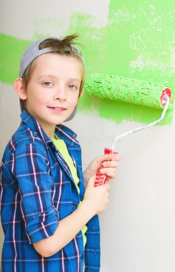 Pojken målar innerväggen av hemmet arkivbilder